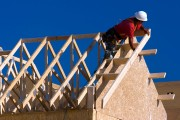 a carpenter building a house, working on roof joists