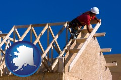alaska map icon and a carpenter building a house, working on roof joists