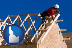 idaho map icon and a carpenter building a house, working on roof joists