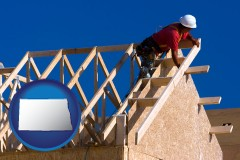 north-dakota map icon and a carpenter building a house, working on roof joists