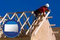 south-dakota map icon and a carpenter building a house, working on roof joists