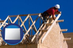 wyoming map icon and a carpenter building a house, working on roof joists